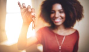 Portrait of a young woman holding up the keys to a new home